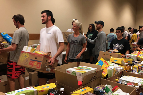 Basketball players assist students during the food giveaway event
