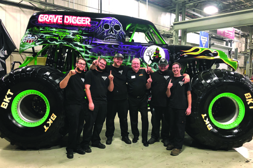 UNOH Graduates and Monster Jam Employees stand with UNOH President, Dr. Jeffrey Jarvis